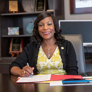Barbara Cooper Sitting at a Desk