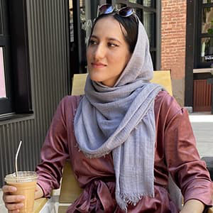 Hussna Yasini at a table drinking coffee