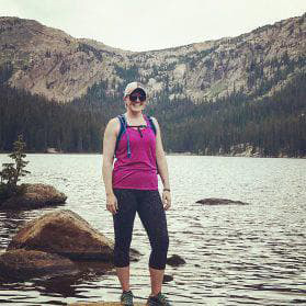 Kristen Freaney standing in front of a lake with mountains behind