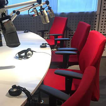 Recording studio with microphones and red chairs